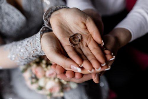 recien-casados-sostienen-anillos-boda-sus-manos_8353-9172